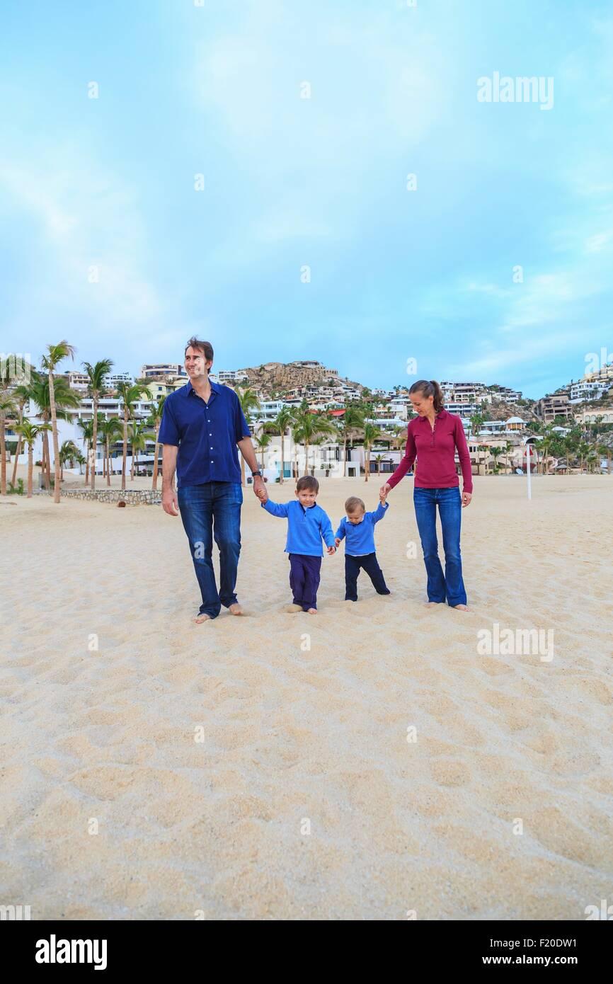Junge Familie, am Strand, gehen Hand in Hand Stockbild