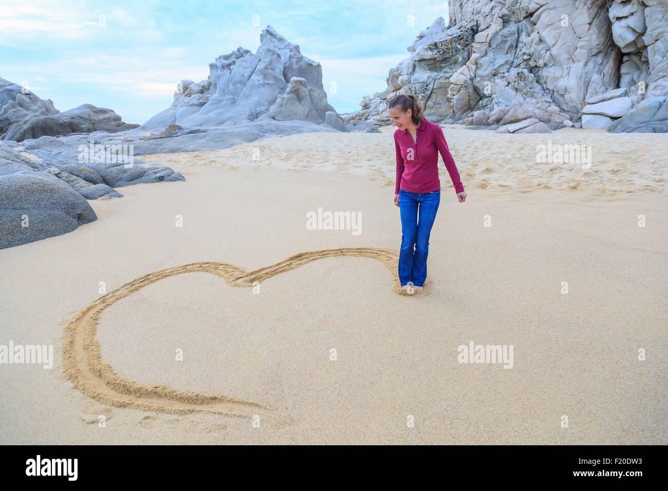Mitte Erwachsene Frau am Strand, Zeichnung Herzform mit Füßen Stockbild
