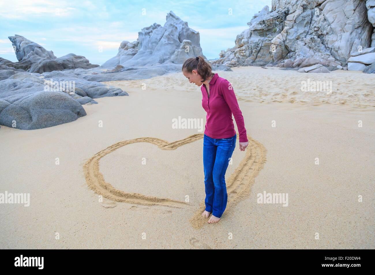 Mitte Erwachsene Frau am Strand, Zeichnung Herzform mit Füßen Stockfoto