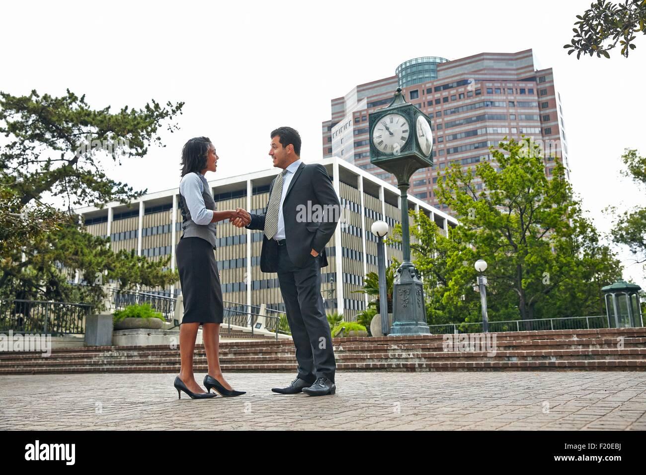 Voller Länge Seitenansicht von Geschäftsleuten, die Hände schütteln Stockbild