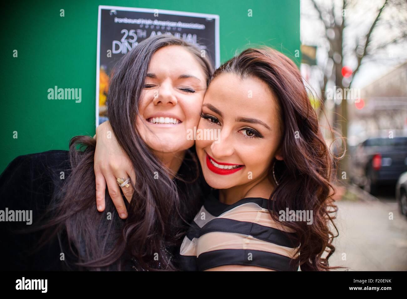 Porträt von zwei junge Erwachsene Freundinnen umarmen auf Straße Stockbild