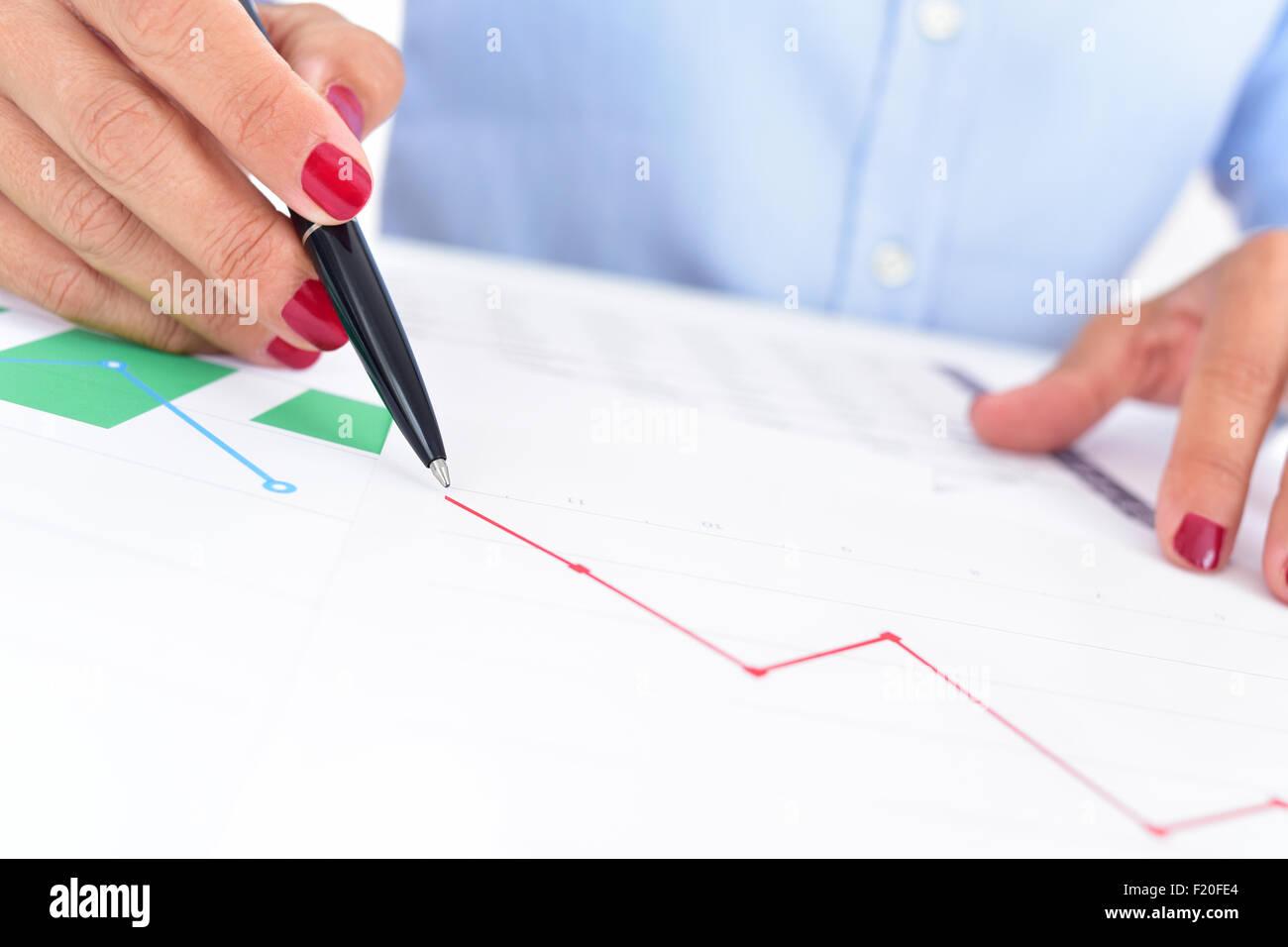 Nahaufnahme von einer Geschäftsfrau an ihrem Schreibtisch voller Grafiken und Diagramme, beobachtet eine Diagramm Stockbild