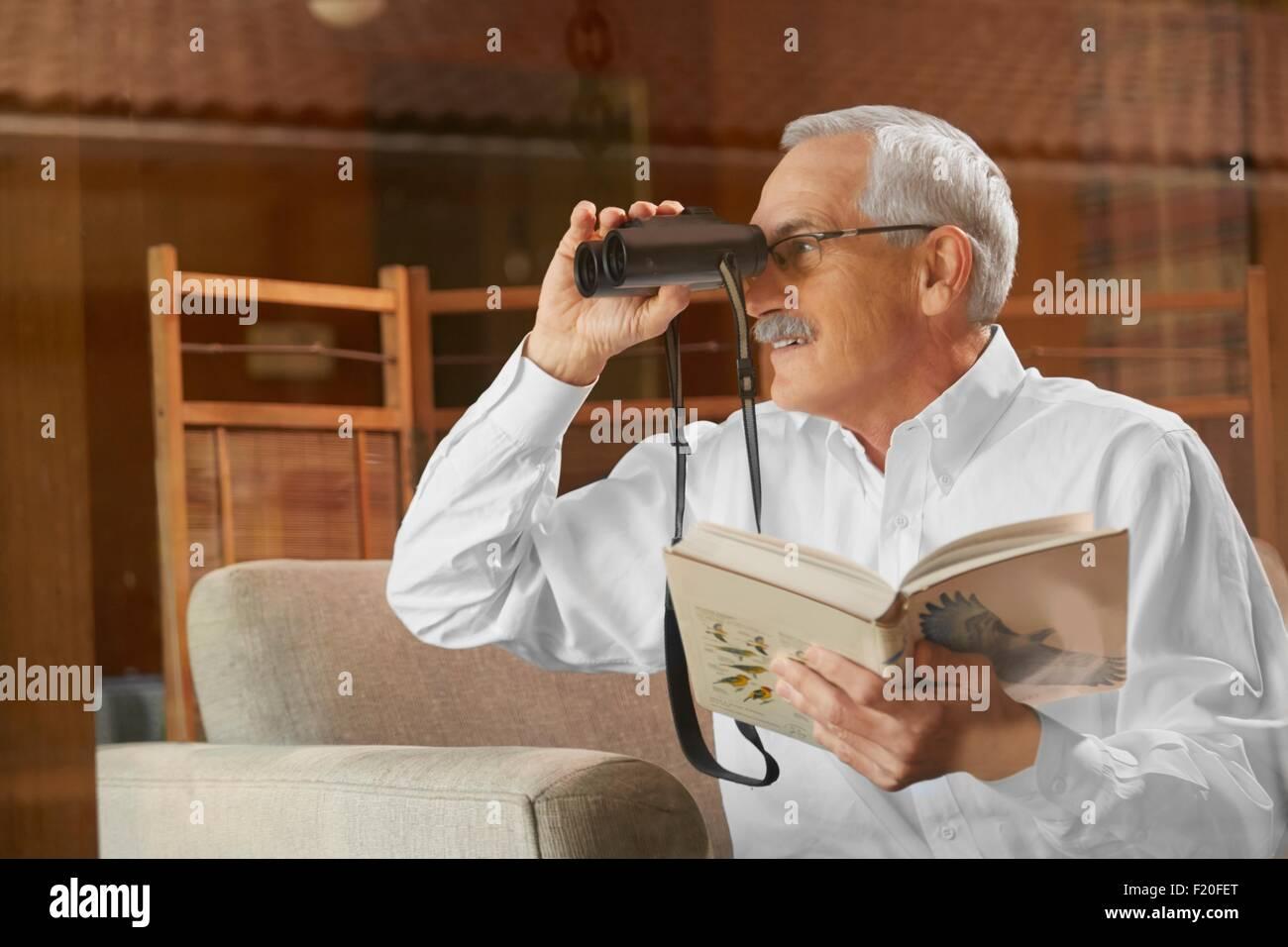 Ältere mann zu hause vogelbeobachtung durch fenster mit dem