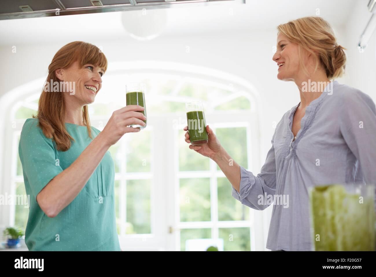 Frauen trinken grünen veganen Smoothie in Küche Stockbild