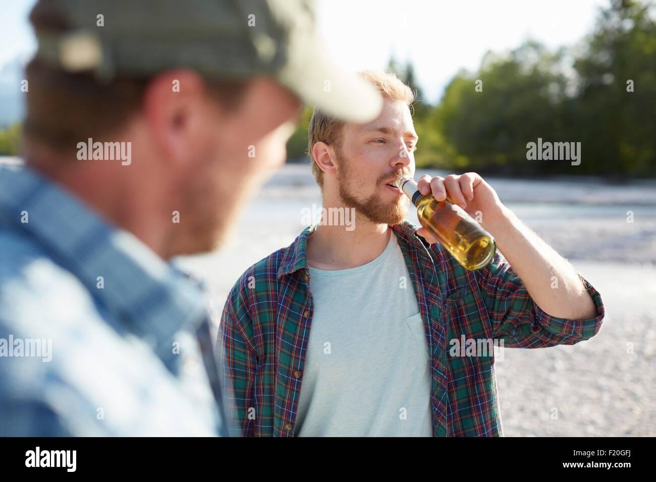 Junger Mann nehmen einen Drink aus einer Bierflasche wegschauen Stockbild