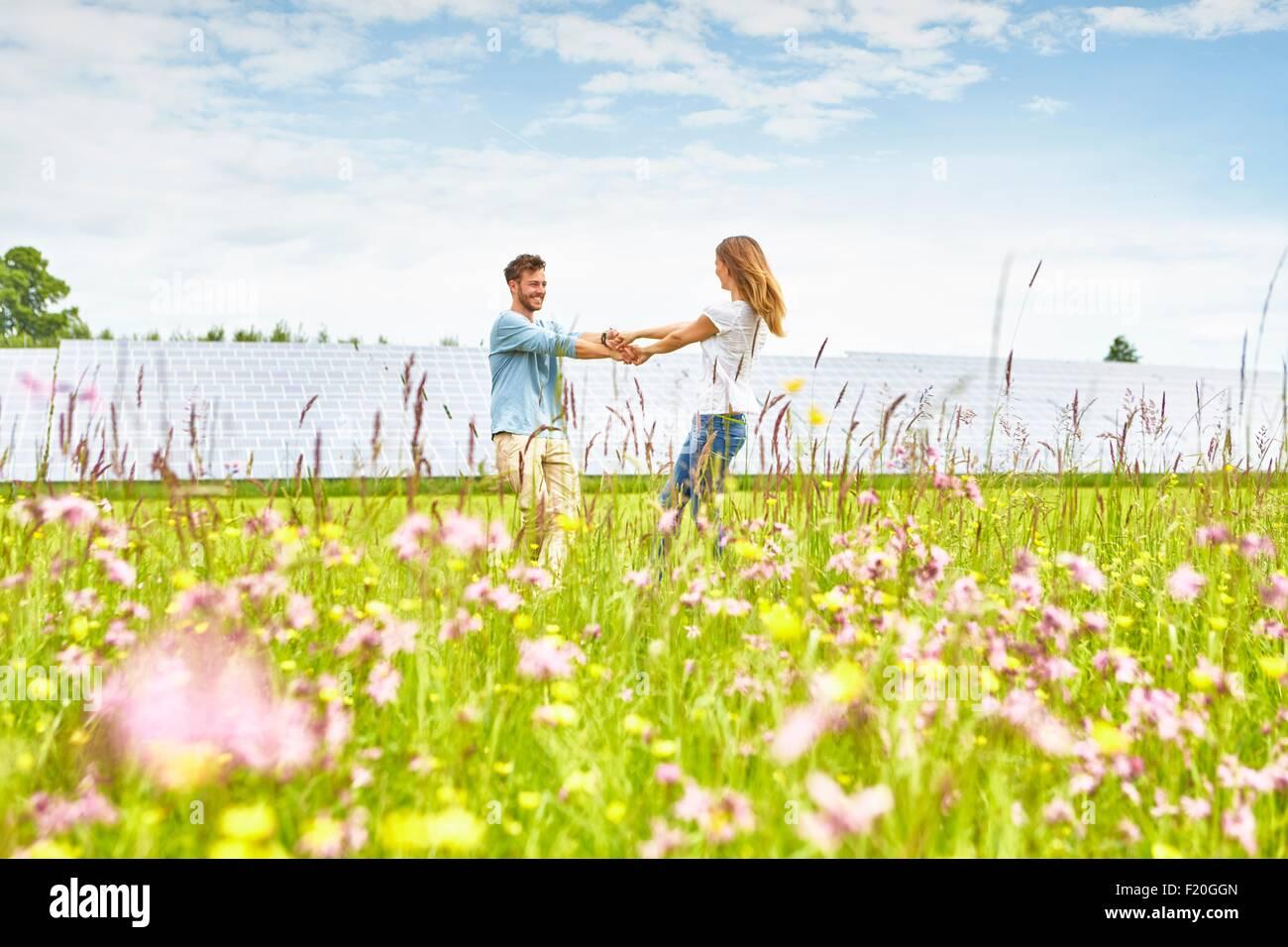 Junges Paar Hand in Hand im Feld neben Solarpark Stockbild