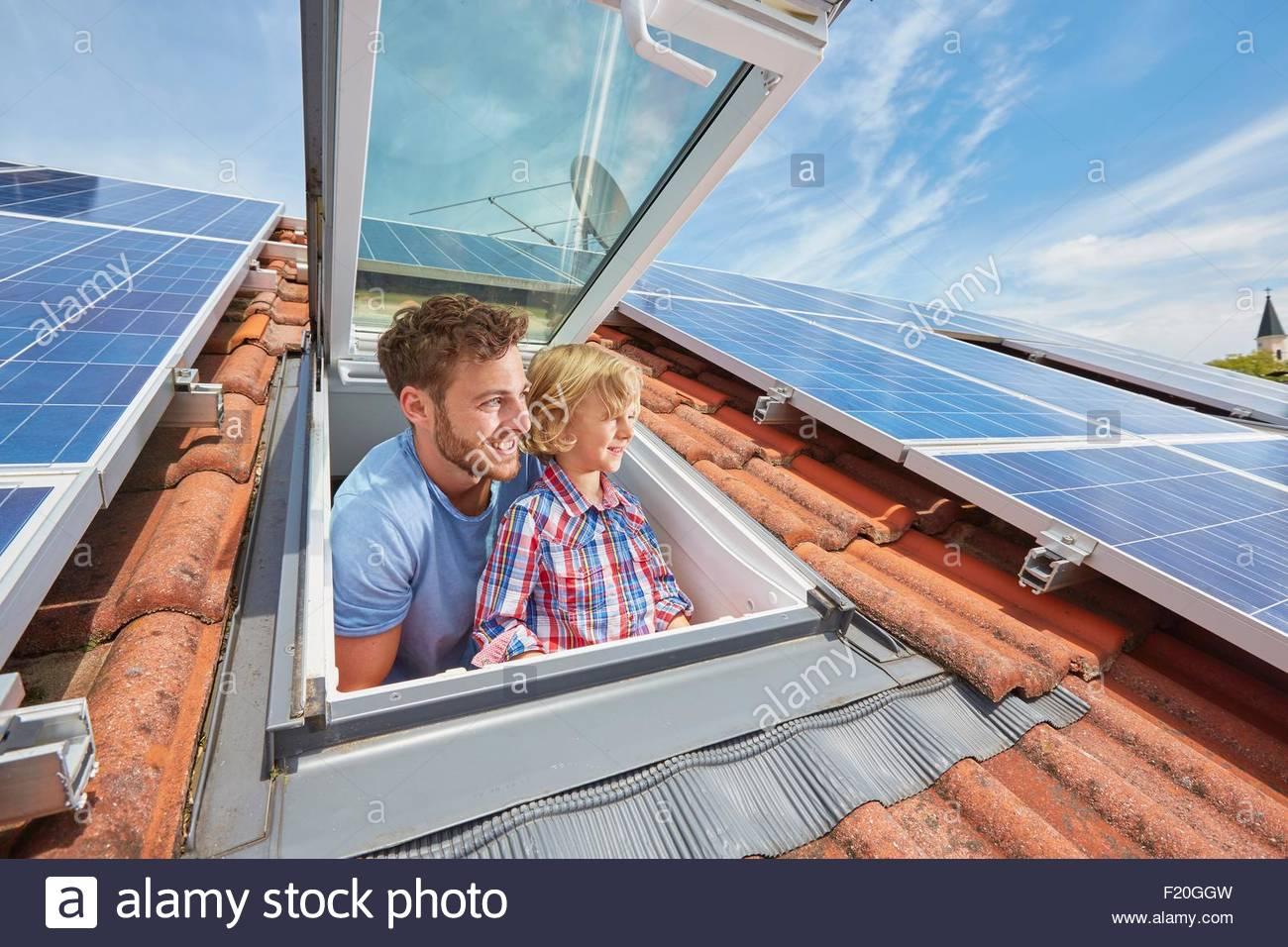 Vater und Sohn Blick aus Fenster von getäfelten Solardach Stockbild