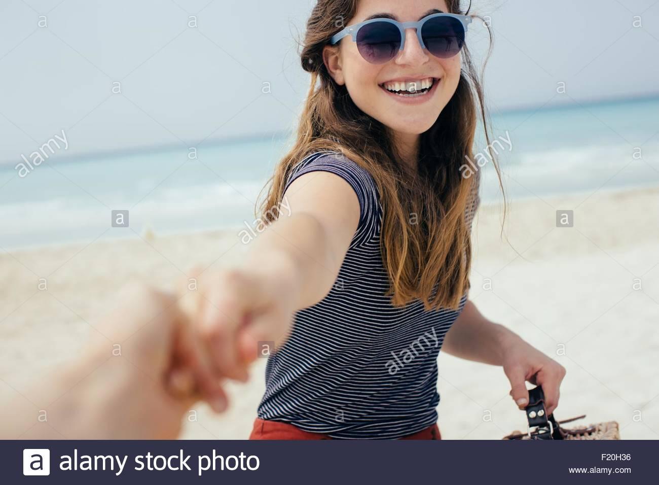 Porträt der jungen Frau, die an beste Freunde Hand am Strand Stockbild