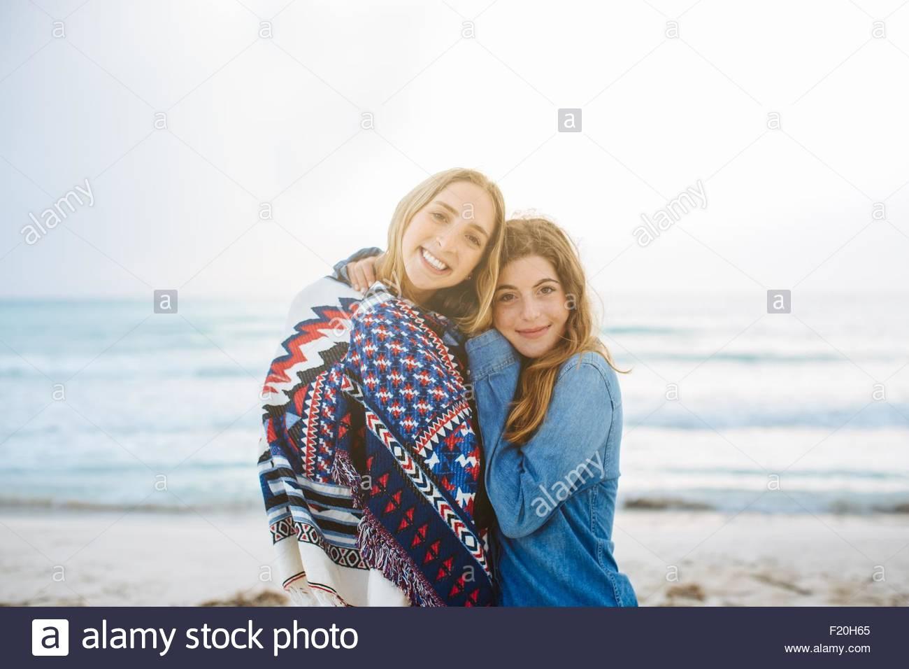 Porträt von zwei jungen Freundinnen umarmen am Strand Stockbild