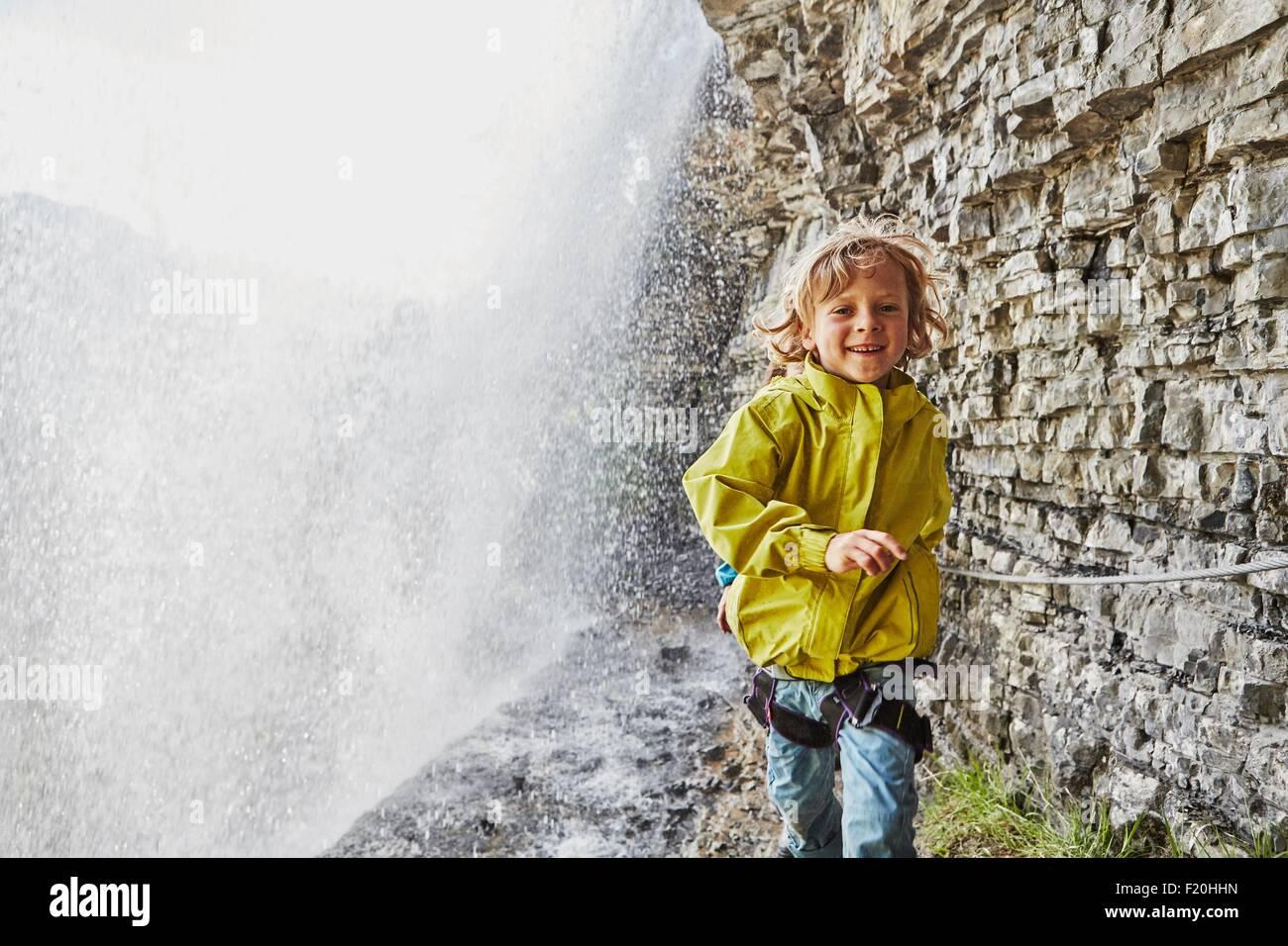 Junge Wandern unter Wasserfall, Lächeln Stockbild