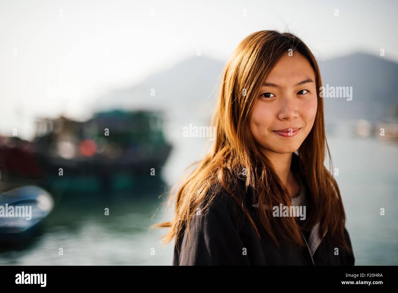 Porträt von Mitte Erwachsene Frau vor Boote auf dem Wasser, Blick auf die Kamera zu Lächeln Stockfoto