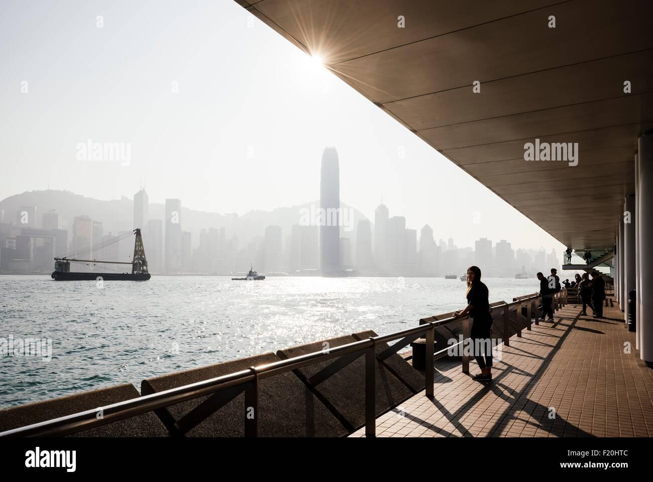 Silhouette Seitenansicht der junge Frau auf der ständigen Suche aus über Wasser im Skyline, Hong Kong, Stockbild