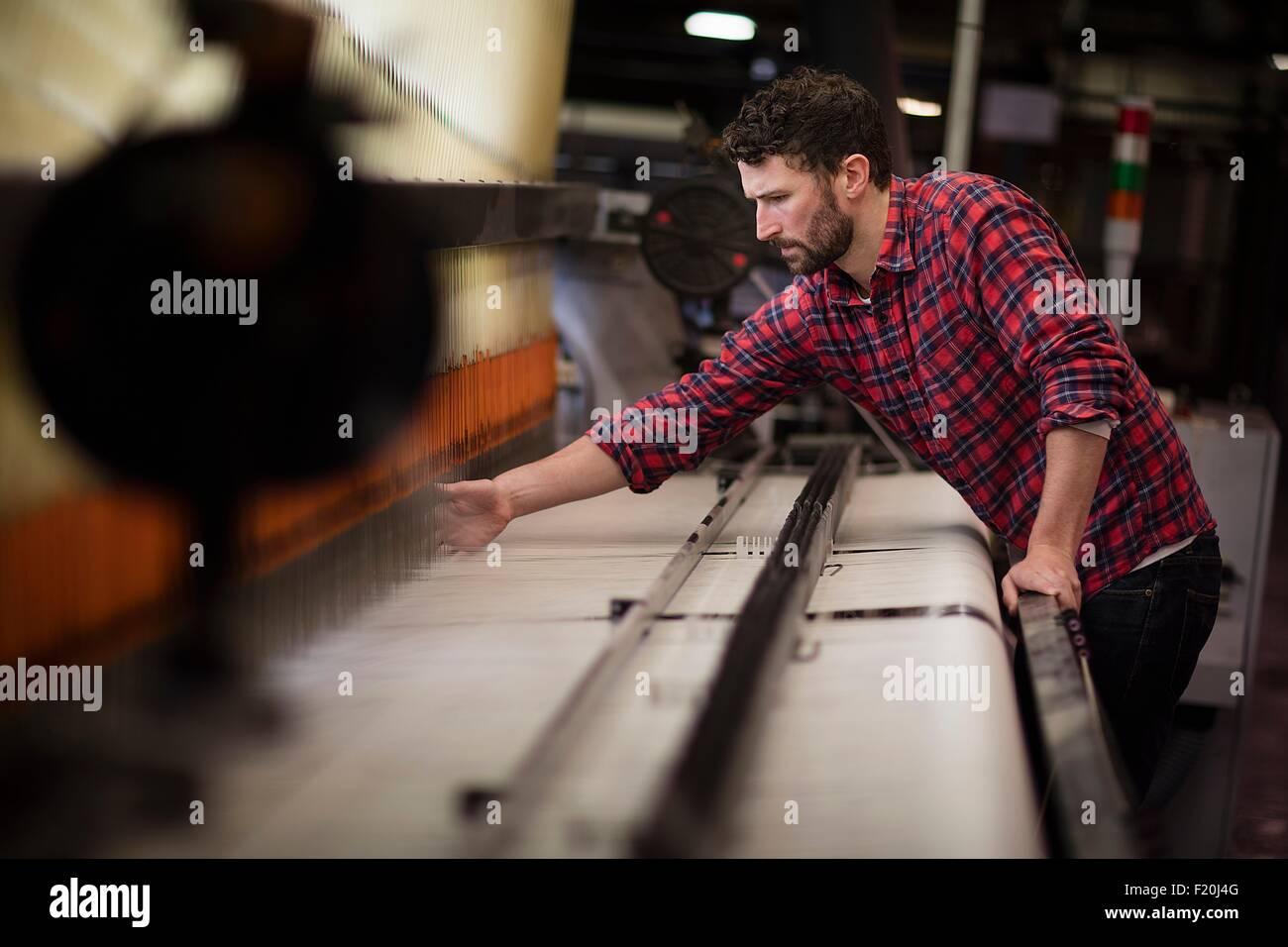 Junge männliche Weberin mit alten Webmaschine in Textilfabrik Stockbild