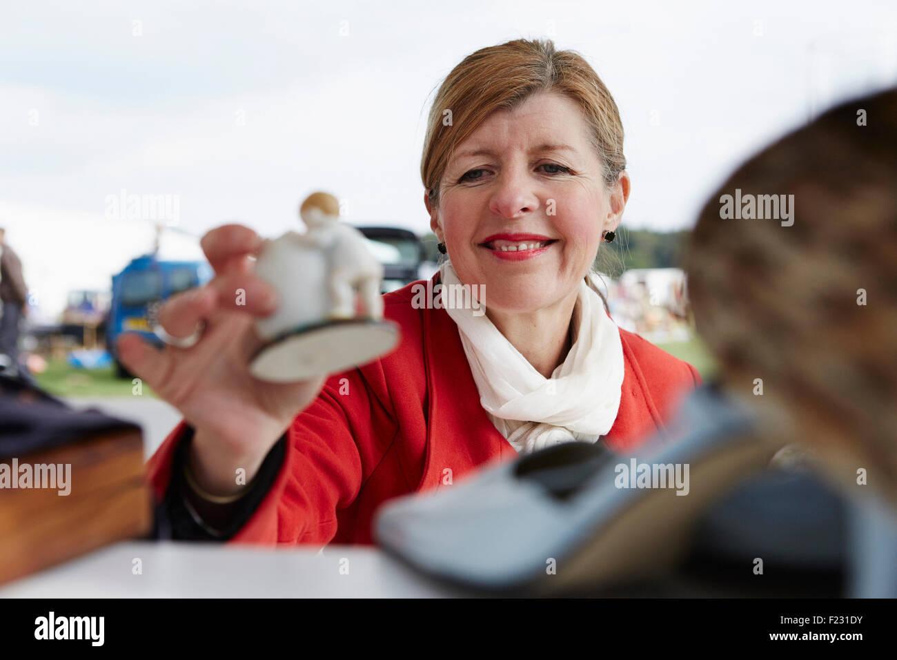 Eine reife Frau in einem roten Mantel hält eine Vintage Porzellanfigur auf einem Flohmarkt. Stockfoto