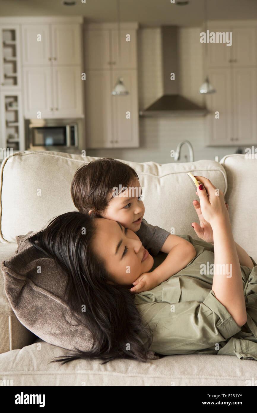 Frau liegt auf dem Sofa kuscheln mit ihrem kleinen Sohn und mit Blick auf ein Handy. Stockfoto