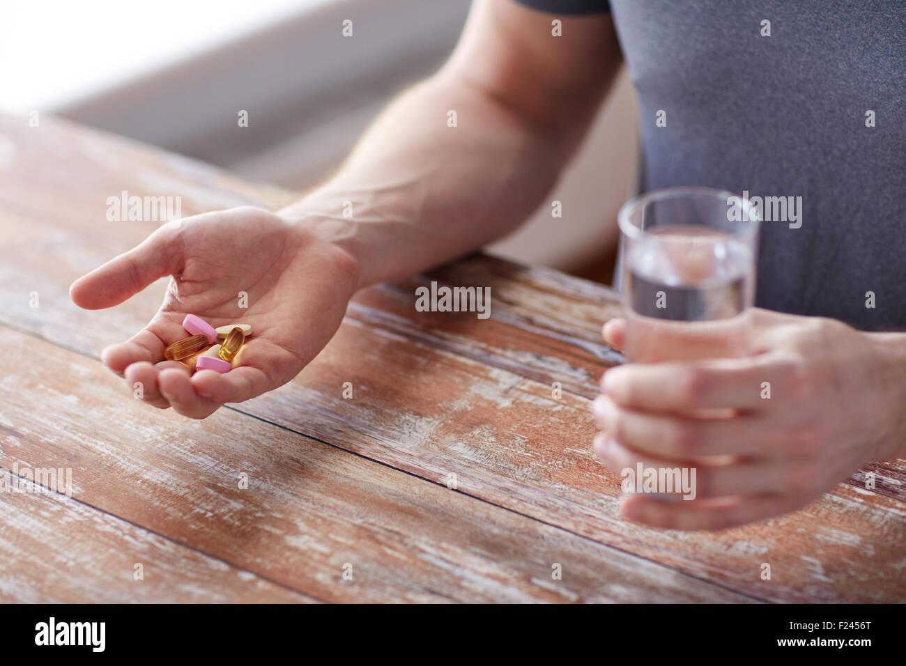 Nahaufnahme von männlichen Händen mit Pillen und Wasser Stockbild