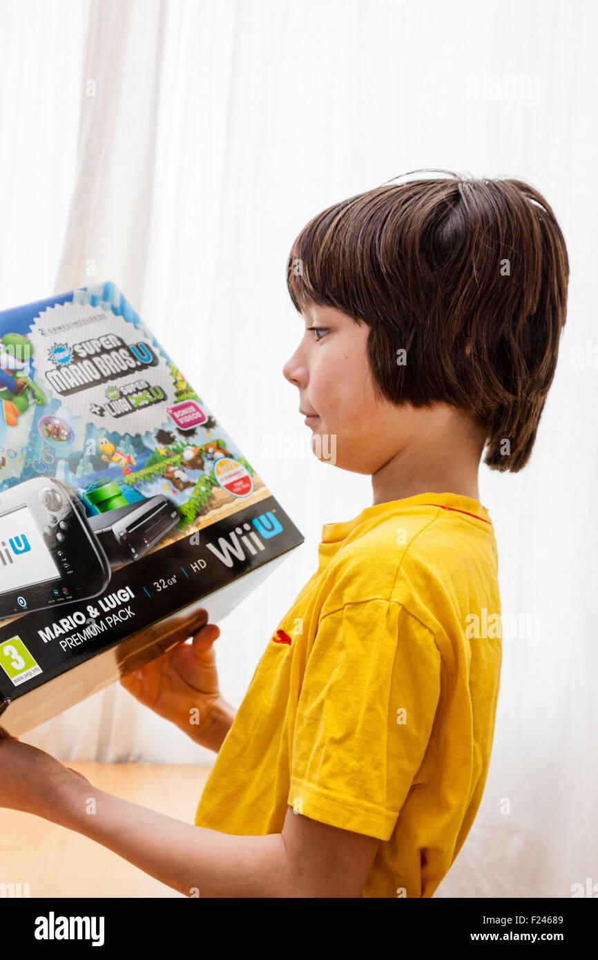 Kaukasische Kind, Tweens, 10 bis 12 Jahre alt, hält in beiden Händen Nintendo Wii U Spiele-Konsole im Stockbild