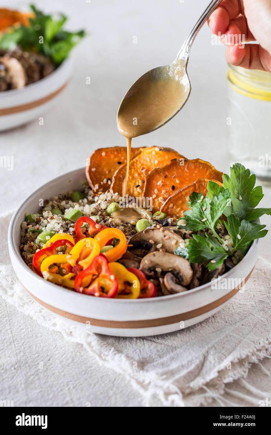 Eine Schüssel mit Quinoa garniert mit Süßkartoffeln, Pilze, Paprika und beträufelt mit Tahini Stockbild