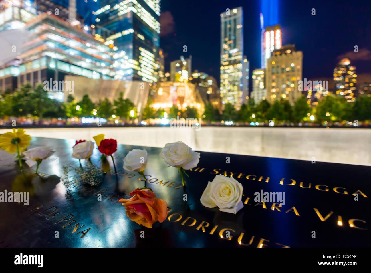 New York, NY - 11. September 2015 - Blumen umgeben den reflektierenden Pools im 911 Memorial and Museum am 13. Jahrestag Stockbild