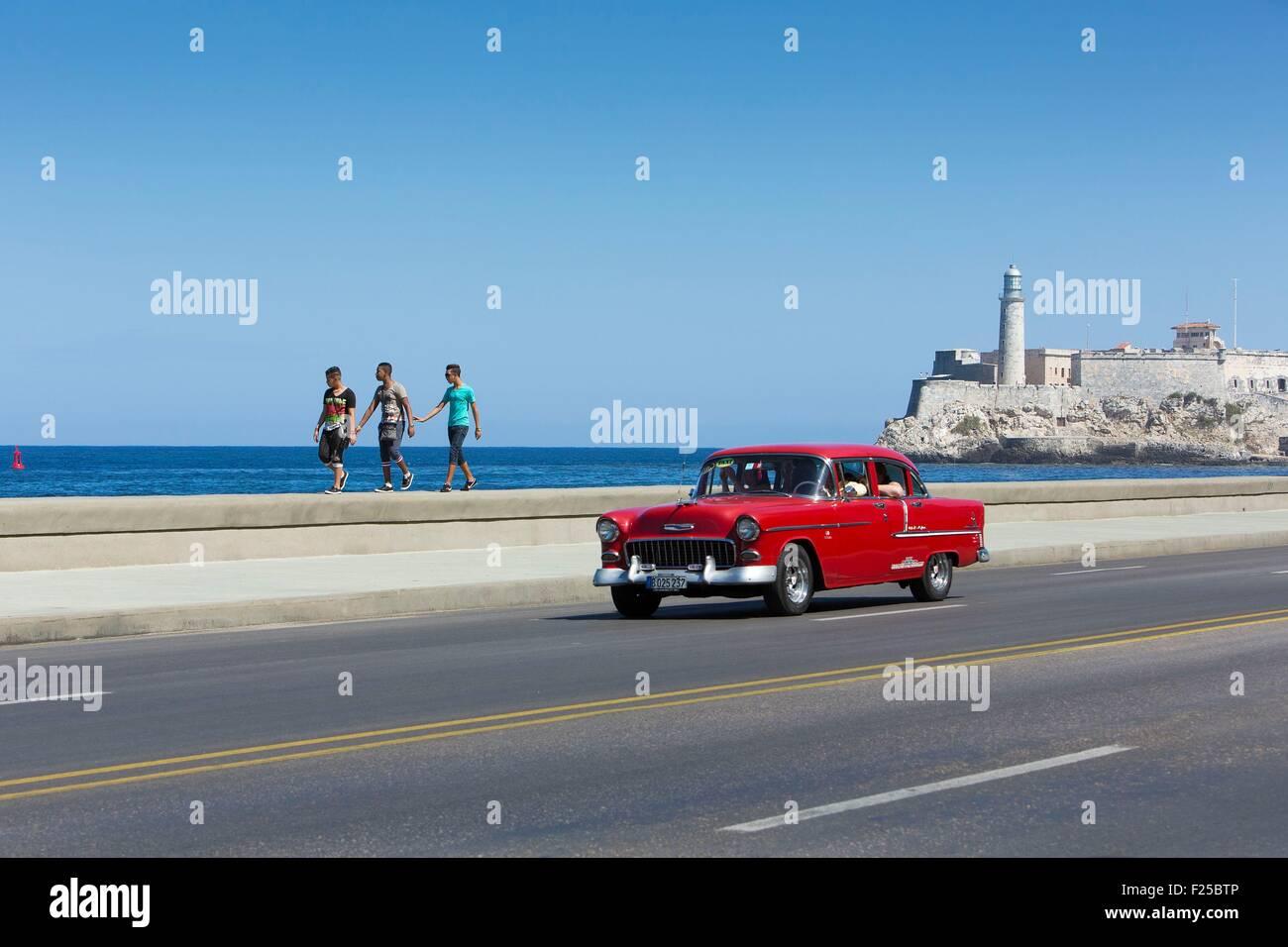 Kuba, Ciudad De La Habana Provinz, La Havanna, amerikanisches Auto auf dem Malecon und der Leuchtturm von dem Castillo Stockbild