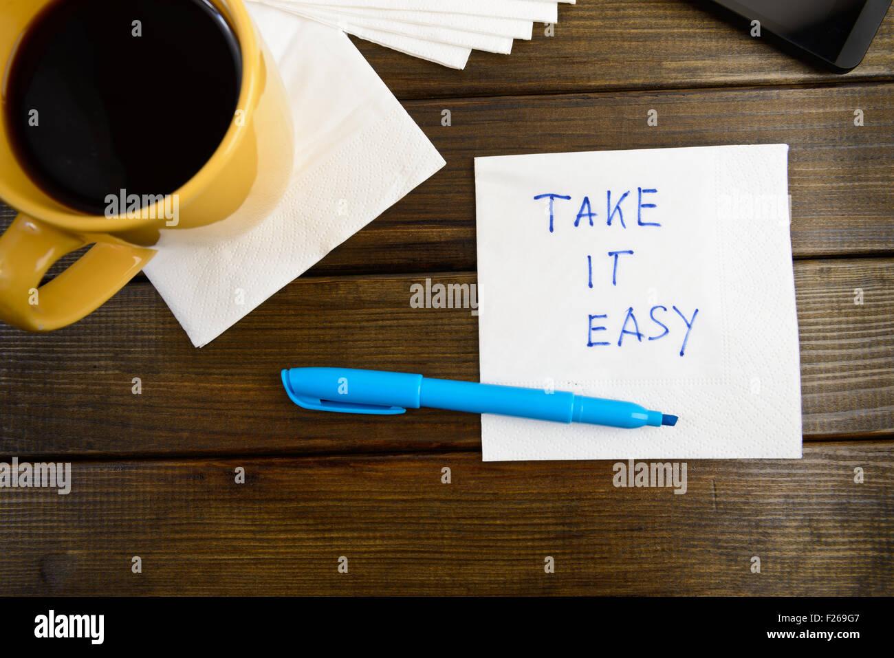 Nimm es leicht - Handschrift auf einer Serviette mit einer Tasse Kaffee Stockbild