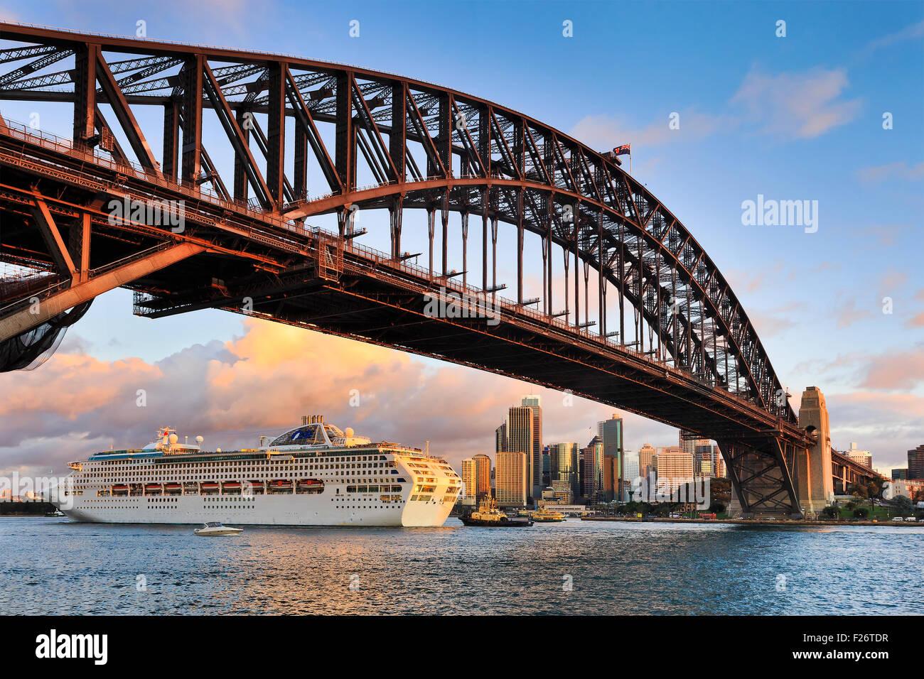 Übergroße Ozean Kreuzfahrtschiff vorbei unter der Sydney Harbour Bridge bei Sonnenuntergang hintergründig Stockbild