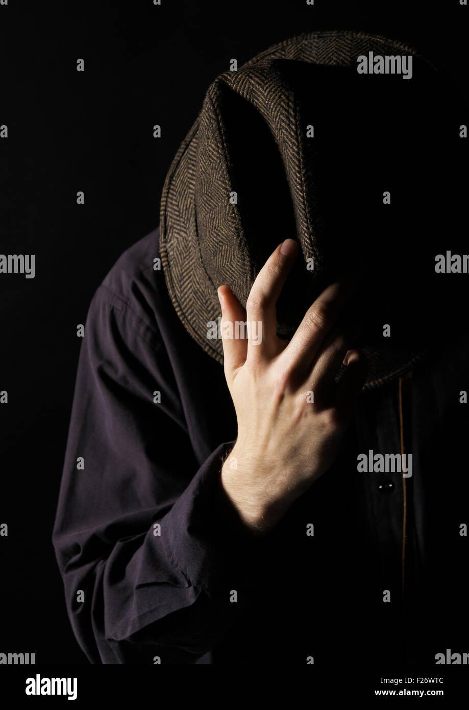 Ein Mann mit einem Hut, bedeckte sein Gesicht. Stockbild