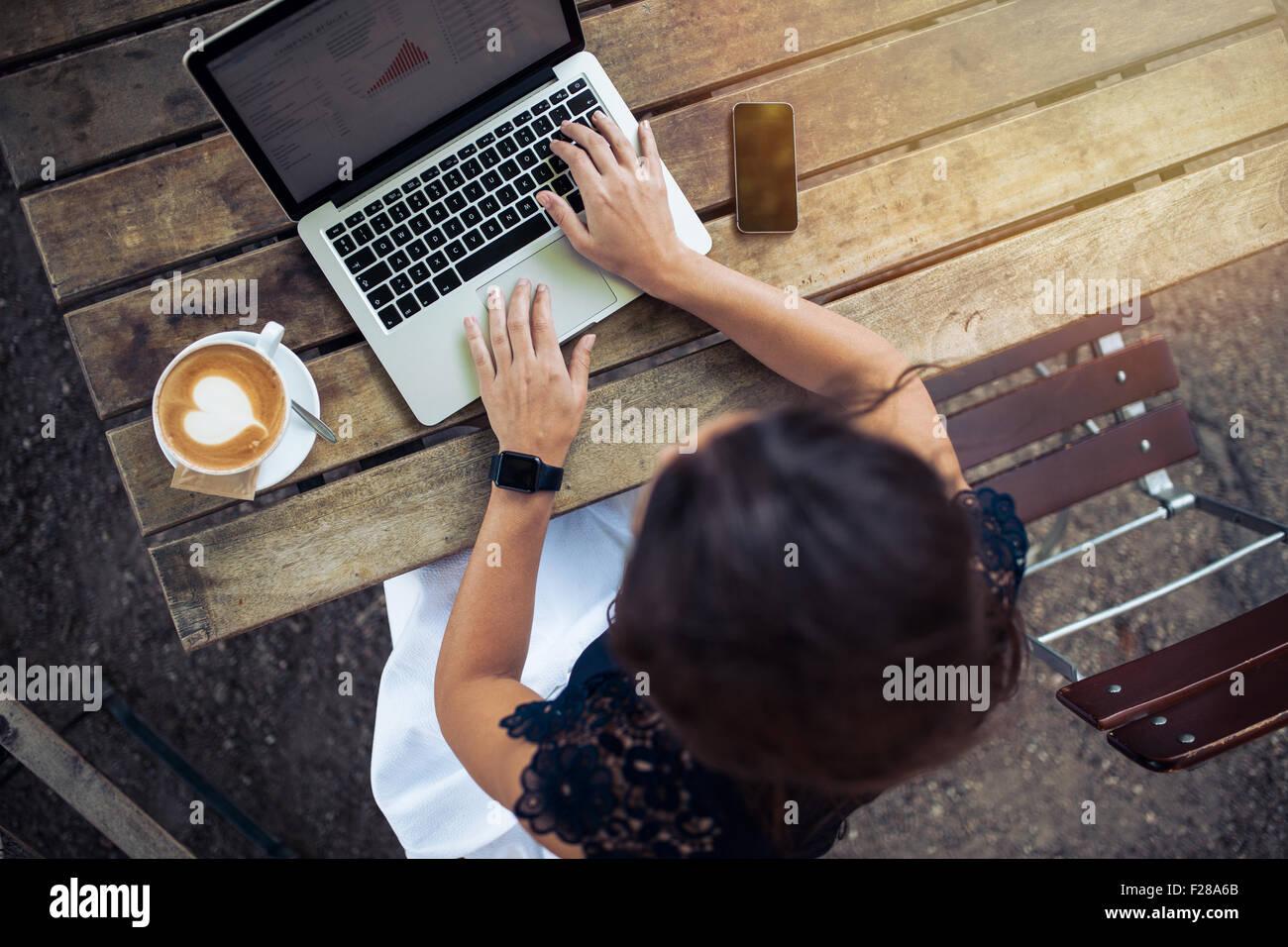 Draufsicht der Weibchen mit ihrem Laptop in einem Café. Overhead Schuss von junge Frau sitzt an einem Tisch Stockbild