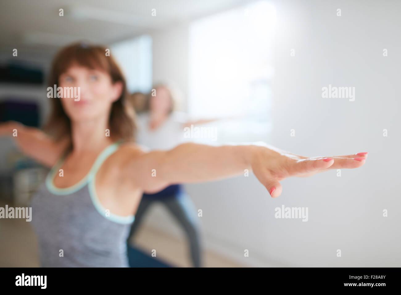 Frau streckte ihre Arme am Yoga-Kurs. Fitness Trainer darstellende Yoga in Krieger darstellen. Virabhadrasana. Auf Stockbild