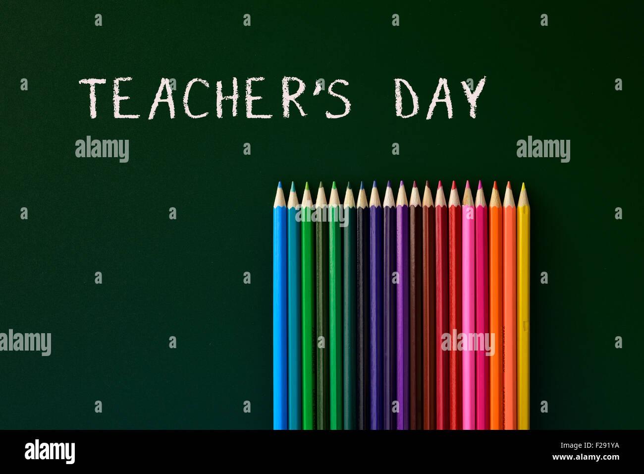 einige farbige Stifte in verschiedenen Farben und die Text-Lehrer-Tag in eine grüne Tafel geschrieben Stockbild