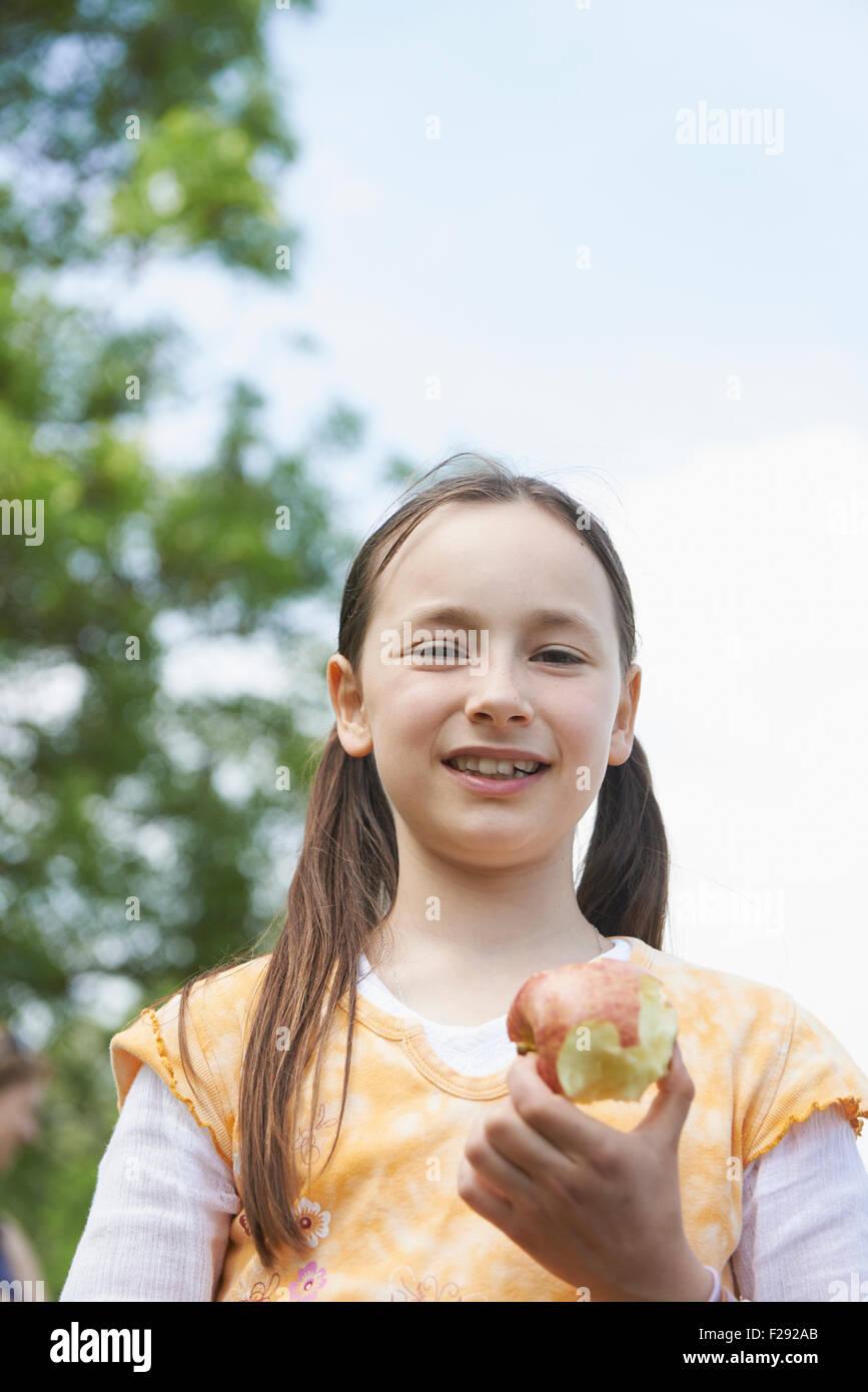 Porträt eines Mädchens hält einen gegessen Apfel, Bayern, Deutschland Stockbild