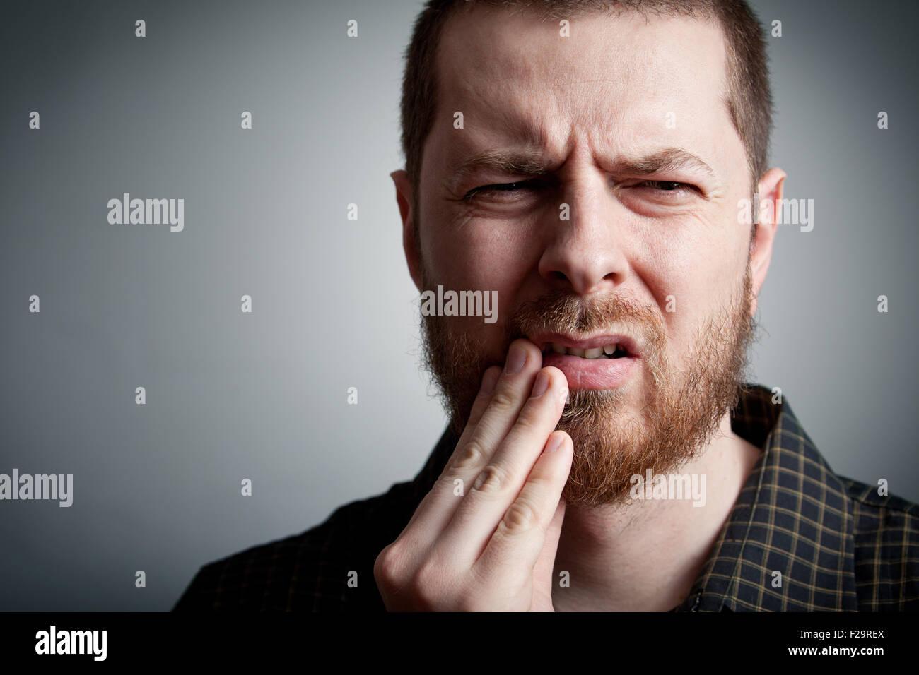 Zahnschmerzen - leidenden jungen Menschen mit Zahnprobleme Stockbild