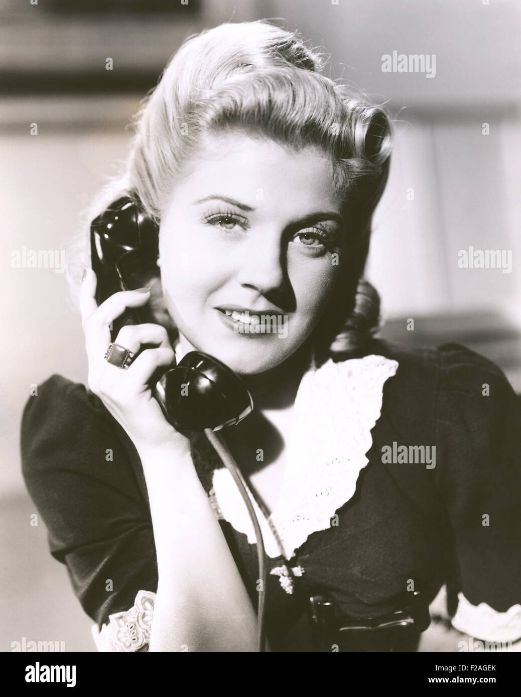 Blonde Frau hält Telefonhörer (OLVI008_OU144_F) Stockbild
