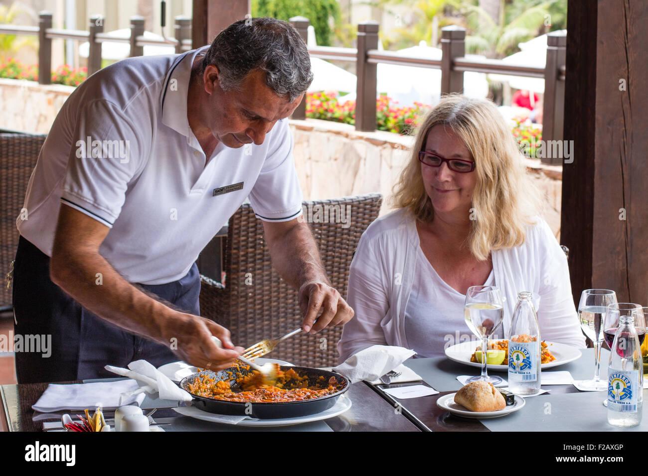 Spanische Kellner servieren Paella weibliche Diner / Tourist. Fuerteventura, Kanarische Inseln. Stockbild