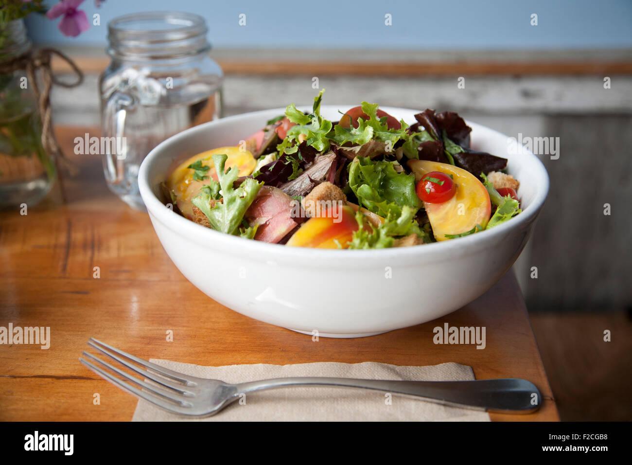 Seitenansicht der Salat in weiße Schüssel mit Gabel, Serviette, Stockbild