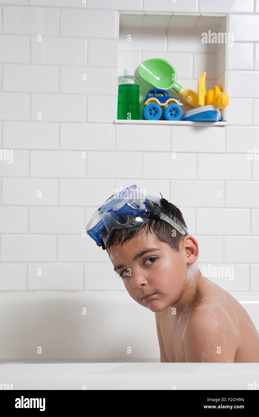 kleiner Junge mit einer Brille auf die Stirn sitzt in der Badewanne und befasst sich mit der Kamera Stockbild