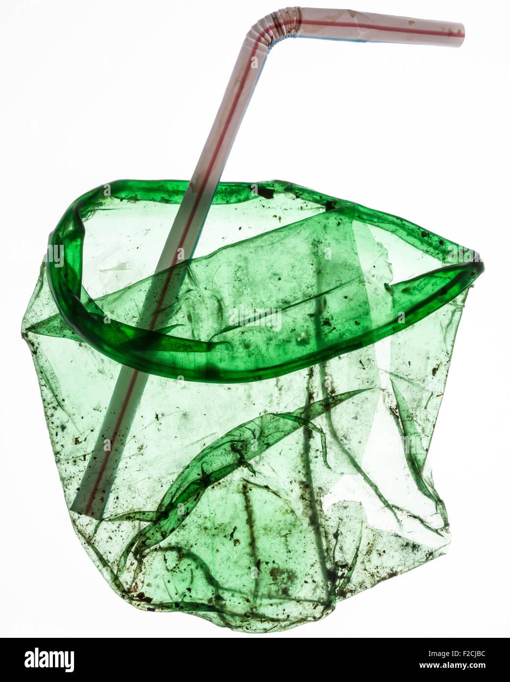 abgeflachte, schmutzig grün transluzent Plastikbecher mit gebogenen Stroh Stockbild