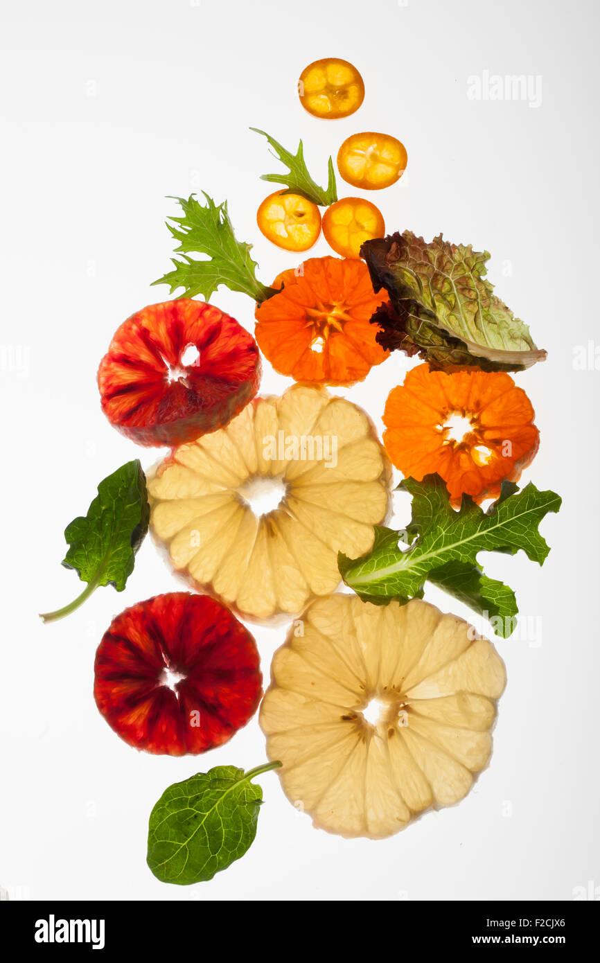 Querschnitt von geschälten Zitrusfrüchten und grünen leuchtet wieder auf weiß Stockbild