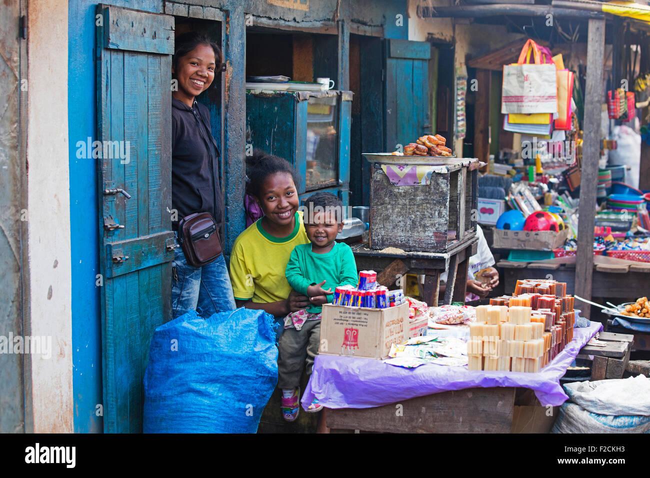 Lächelnd madagassische Mädchen mit Kleinkind vor primitiven Lebensmittelgeschäft in der Stadt Ambalavao, Stockbild