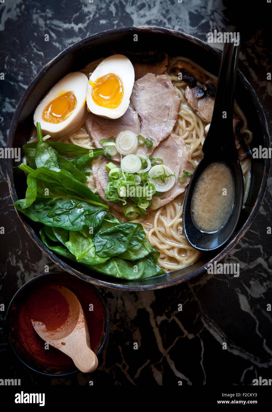 Draufsicht der Ramen mit mit Ei, Spinat, Schweinefleisch und Schweinebauch auf Marmortisch mit Löffel und scharfer Stockfoto