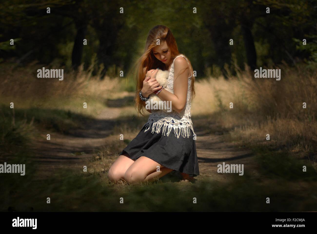Verlorene Seele und Unschuld - Mädchen umarmt Teddybär im Wald weinendes Mädchen im Wald mit Teddy Stockbild