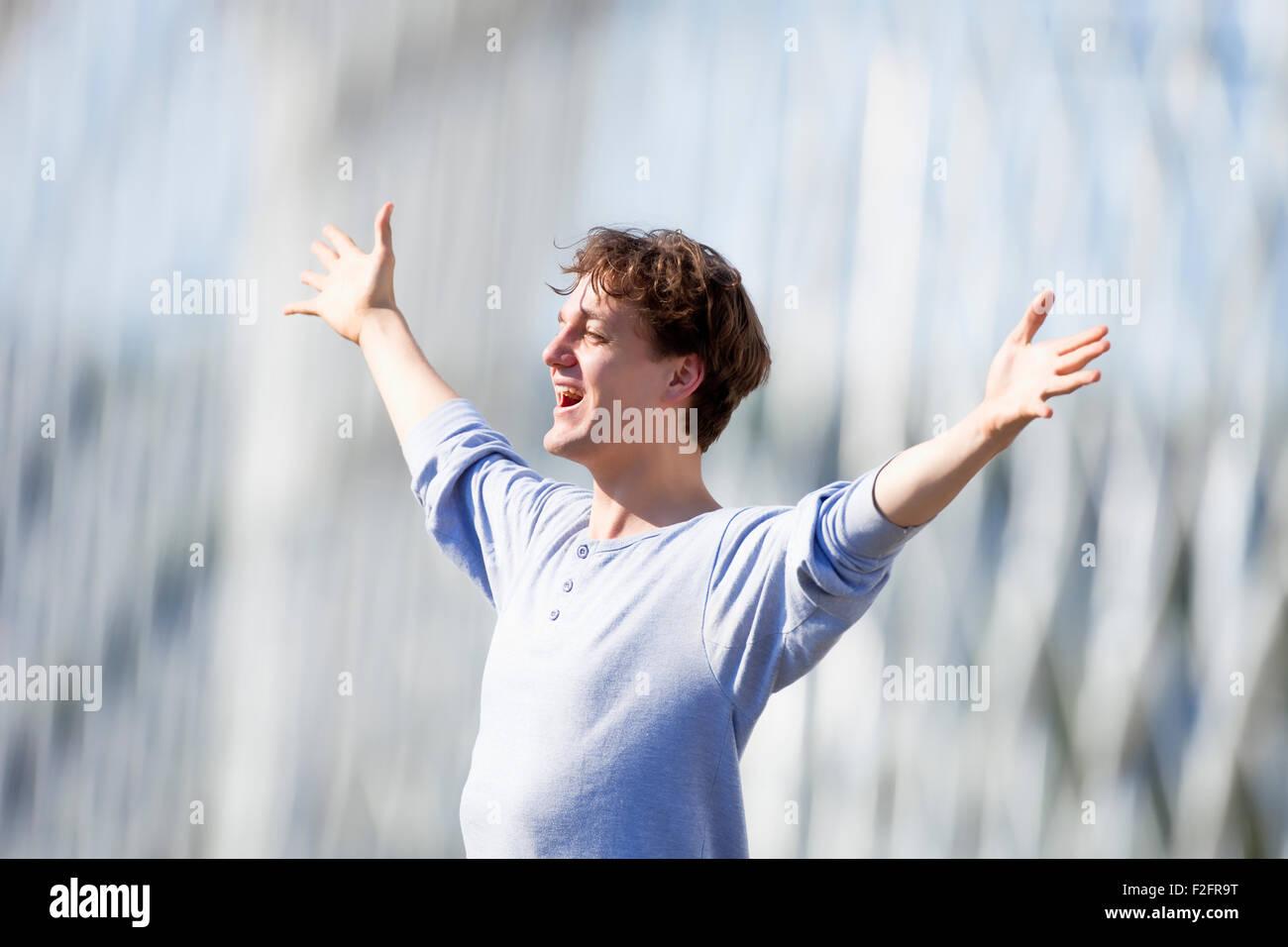 Begeistert junge Mann streckte seinen Arm in Emotion Natur Stockbild