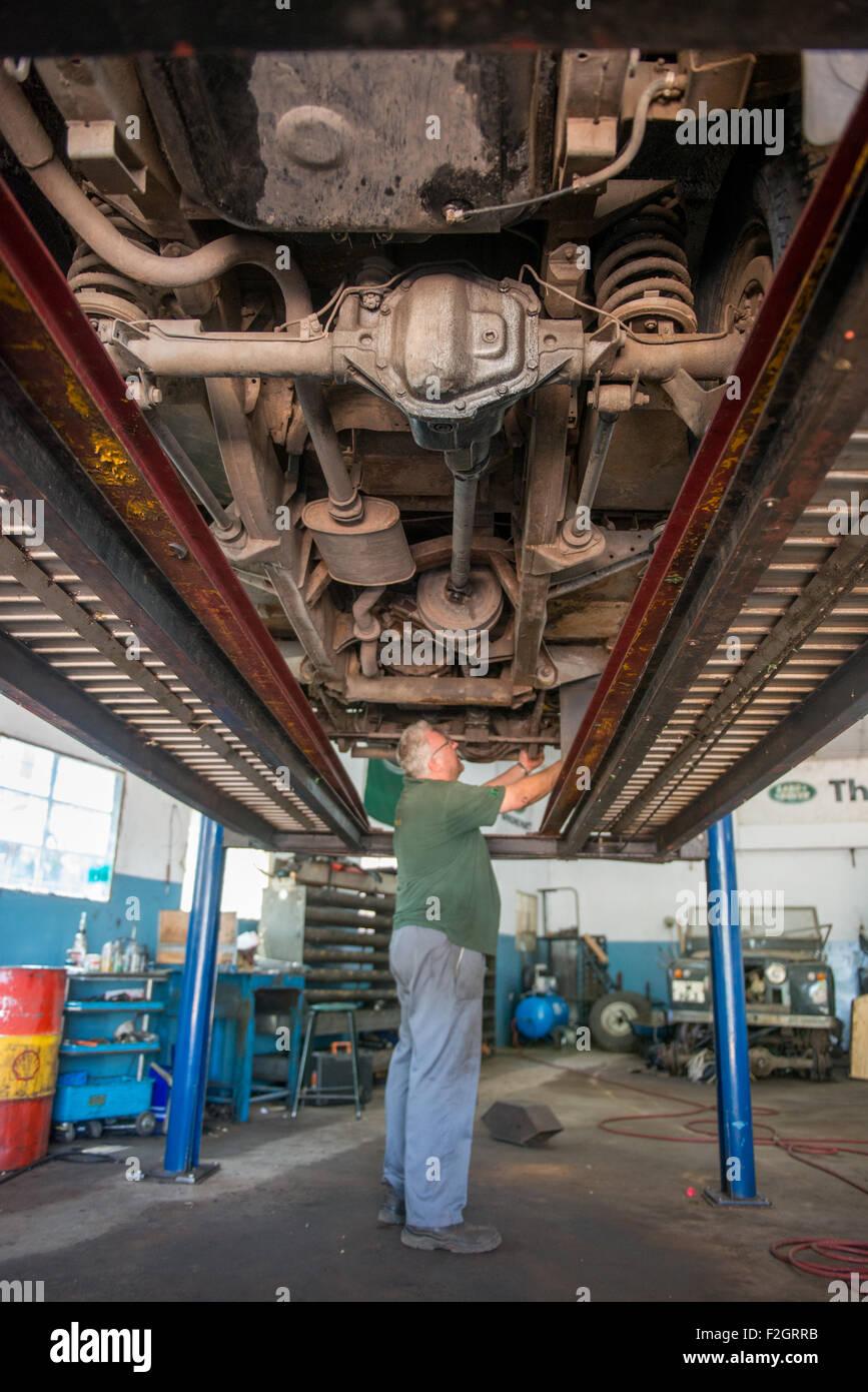 Kfz-Mechaniker arbeiten unter Fahrzeug in seinem Geschäft in Afrika Stockbild