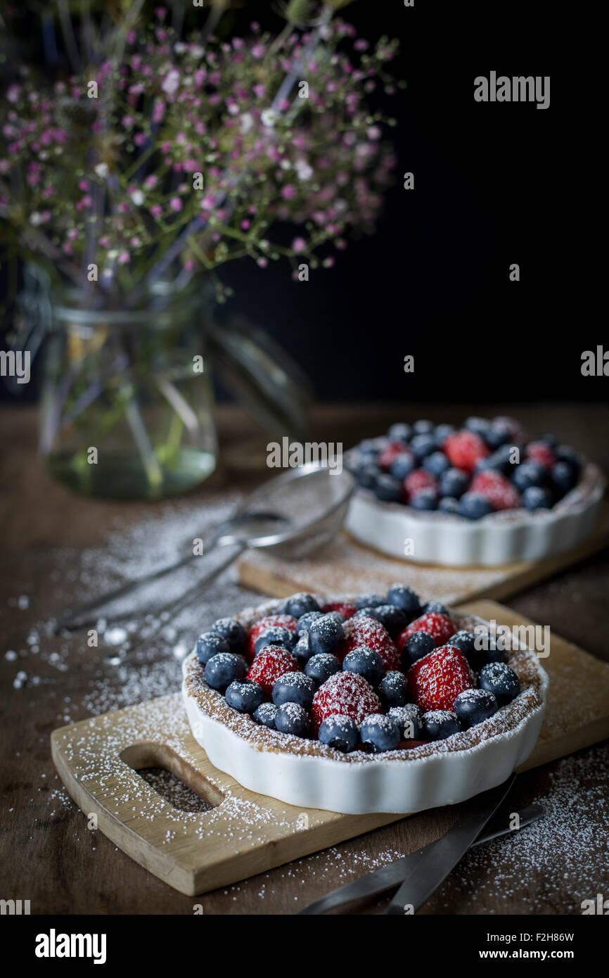 Berry Tartetelets mit Puderzucker in Backformen auf Holzplatten mit Blumenstrauß im Hintergrund Stockbild