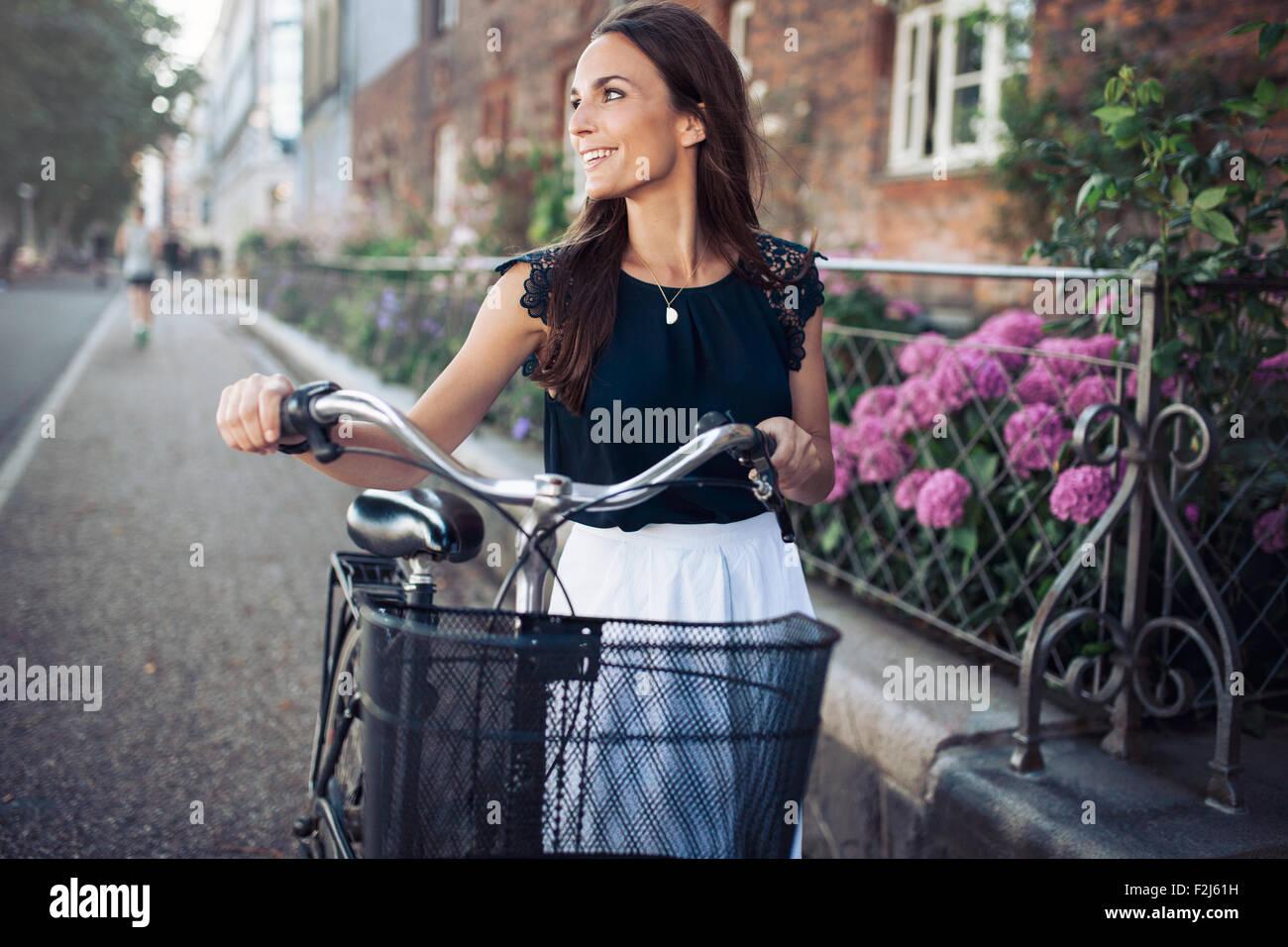 Fröhliche junge Frau wegsehen bei einem Spaziergang auf der Straße mit dem Fahrrad. Weibchen mit einem Stockbild