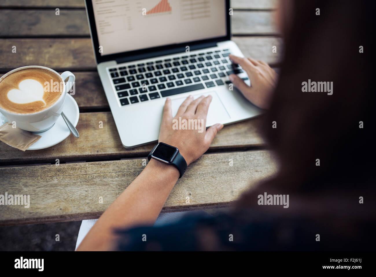 Frau Tippen auf der Tastatur eines Notebooks mit einer Kaffeetasse auf Holztisch. Frauen tragen eine Smartwatch Stockbild