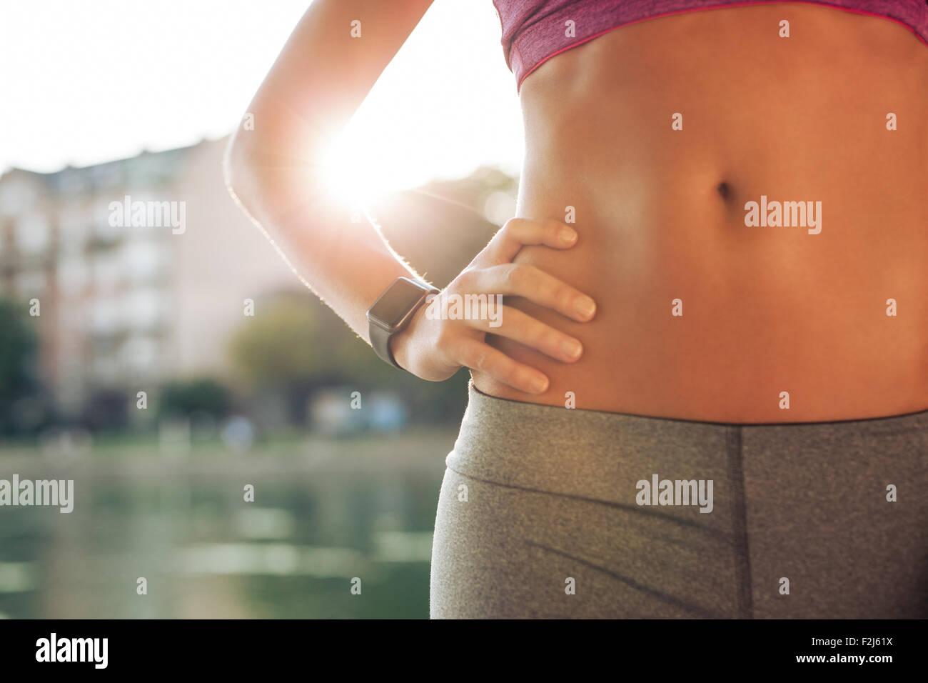 Mittleren Bereich der Torso Fit Frau mit ihren Händen auf den Hüften. Weibliche Läufer tragen Smartwatch Stockbild