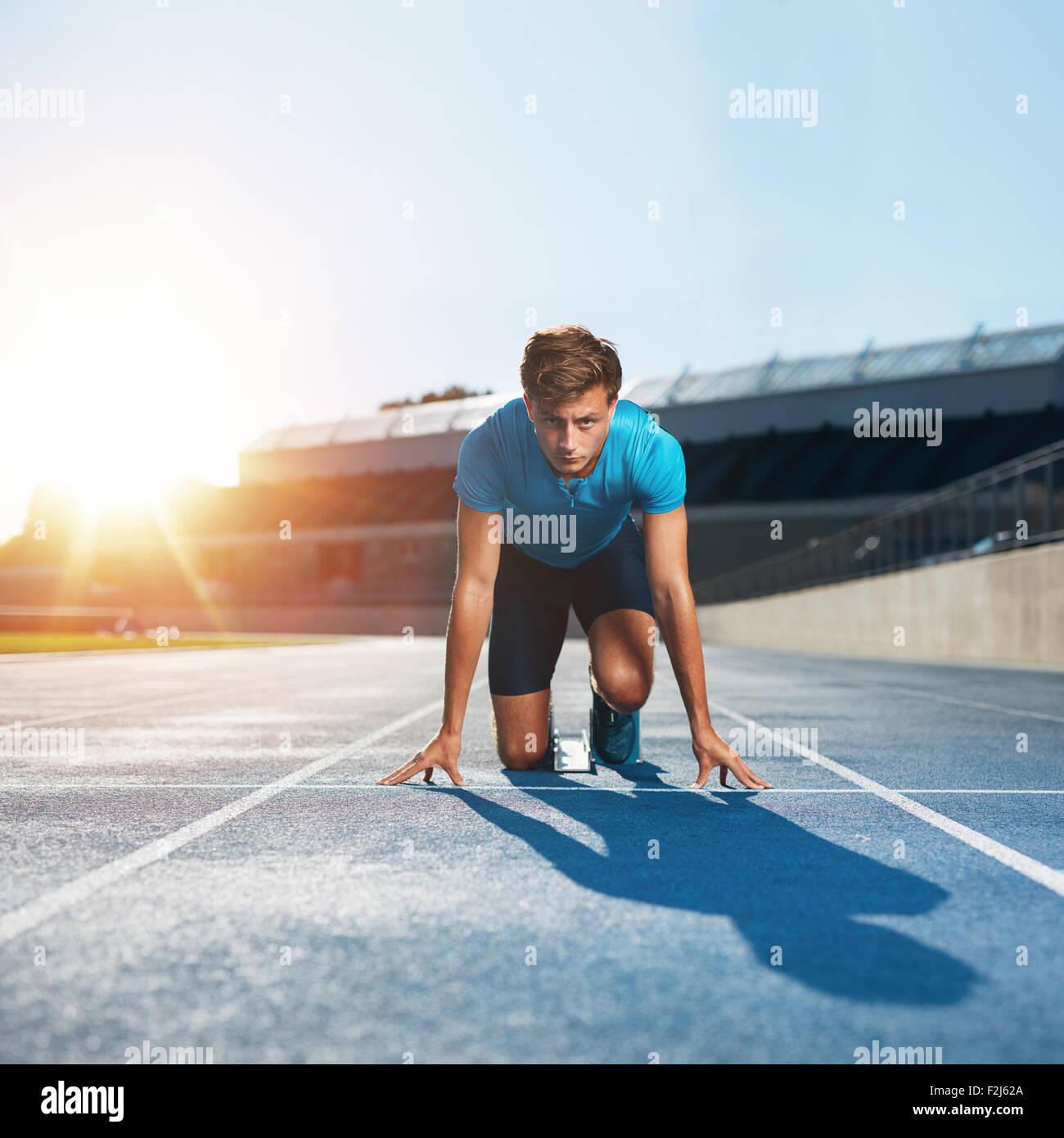 Fit und selbstbewussten Mann in Startposition für den Betrieb bereit. Männliche Athleten kurz vor dem Stockbild