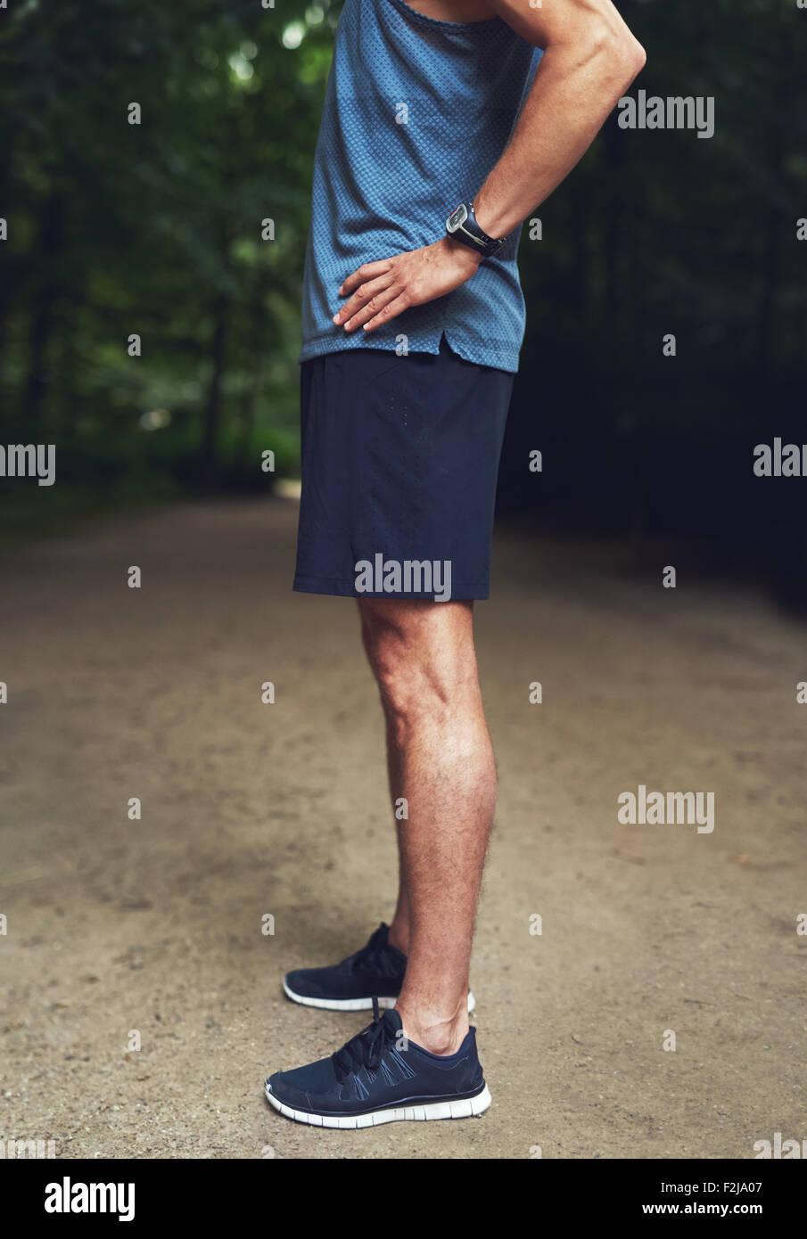 Kopflose Schuss von einem athletischen jungen Mann in Seitenansicht, stehen im Park mit Hand auf Taille. Stockbild