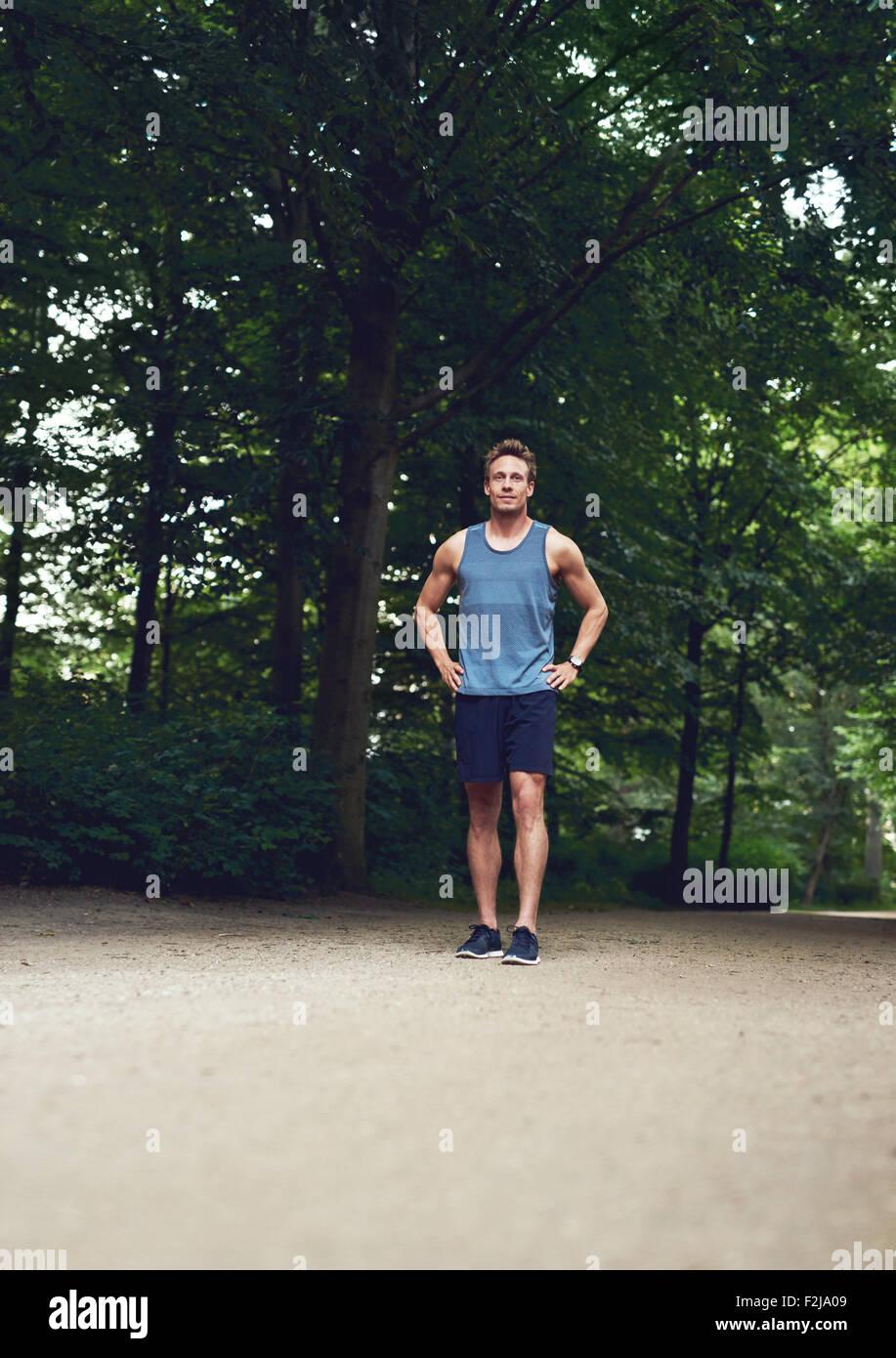 Sportliche junge Mann stehen im Park mit Händen hält seine Taille und suchen in der Ferne. Stockbild